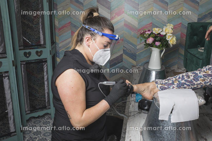 beautician working with mask and protective screen for the virus COVIDの販売画像