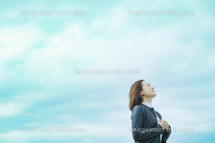 空を見上げるカジュアルな服装のビジネスウーマンの販売画像