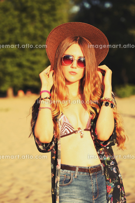 Fashion portrait of beautiful hippie young woman wearing boho chic clothes and summer hat outdoors. Soft warm vintage color tone. Artsy bohemian style.の販売画像