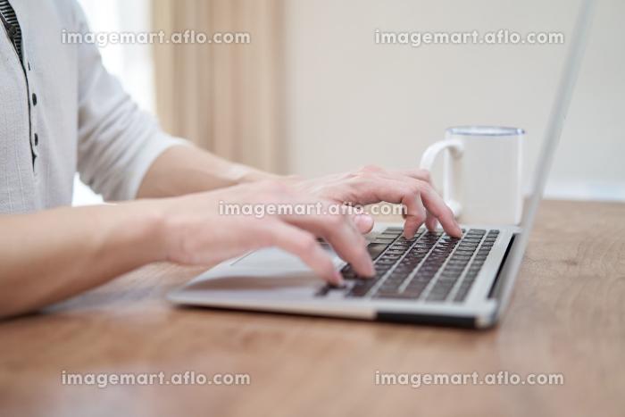 自宅でノートパソコンでタイピングをするアジア人男性の手元の販売画像