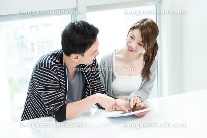 一緒にタブレットPCを見る夫婦の販売画像