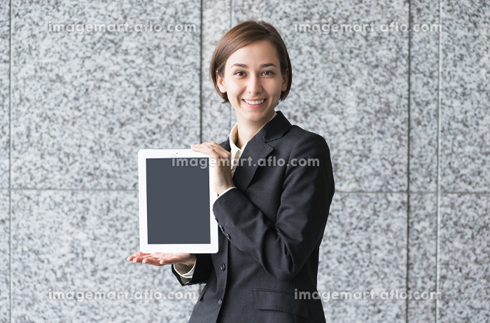 タブレットPCを持つ笑顔の若い女性の販売画像