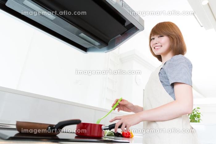 料理をする女性の販売画像