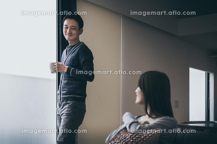 朝のコーヒーを飲みながら会話する幸せなカップルの販売画像