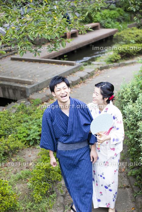緑道を歩く浴衣姿のカップル