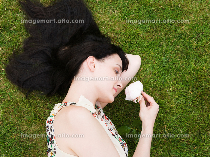 Woman laying on grass, smelling roseの販売画像