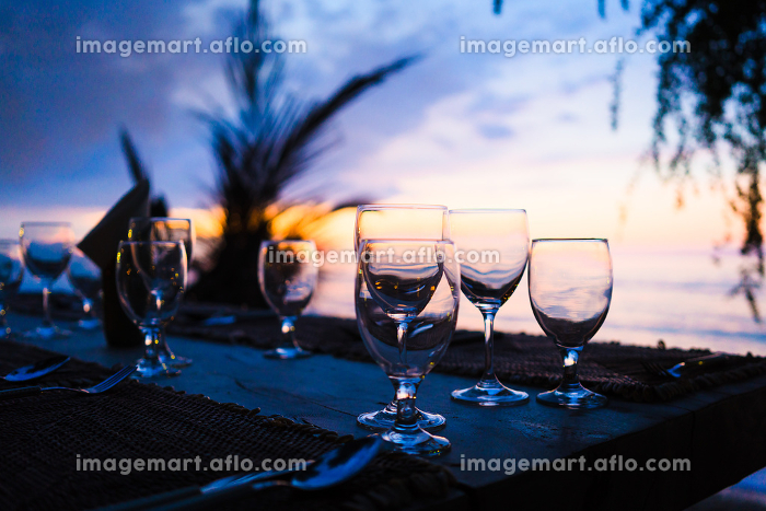 Glasses on table in tropical restaurant at sunsetの販売画像