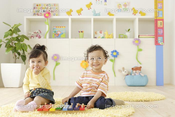 カラフルな子供部屋で楽器で遊ぶハーフの子供たちの販売画像