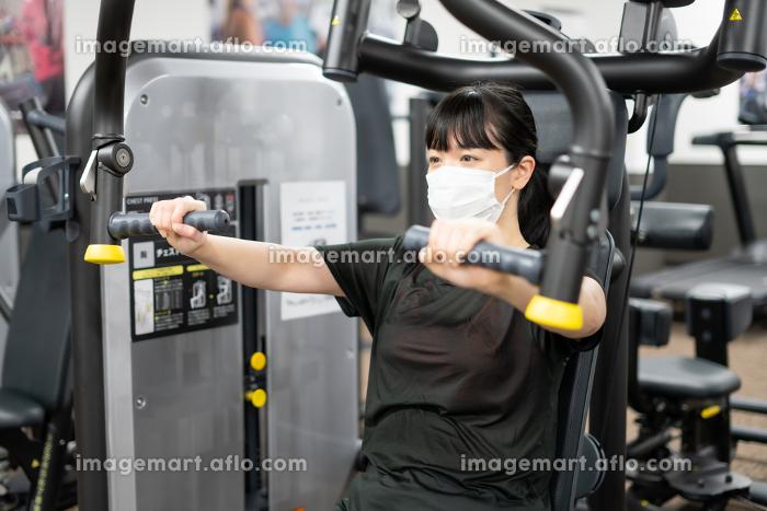 マスクしながらフィットネスジムで胸を鍛える女性の販売画像