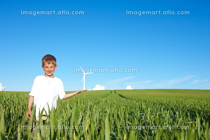Boy on field with wind turbineの販売画像