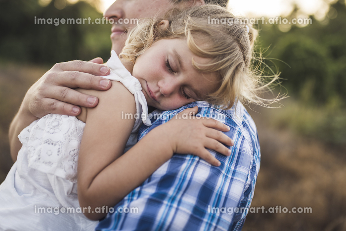 Sleeping child snuggles on her dad's shoulder in a sunny meadowの販売画像