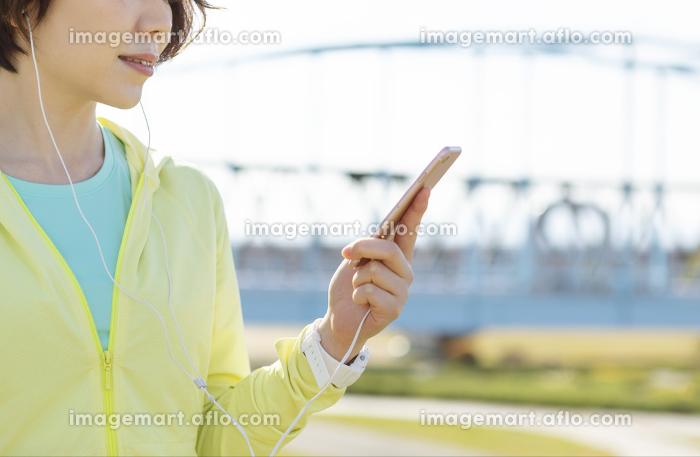 運動中に音楽を聞く女性の販売画像