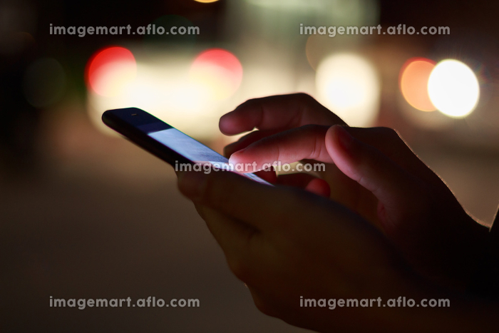 close-up hand using phone in night time on streetの販売画像