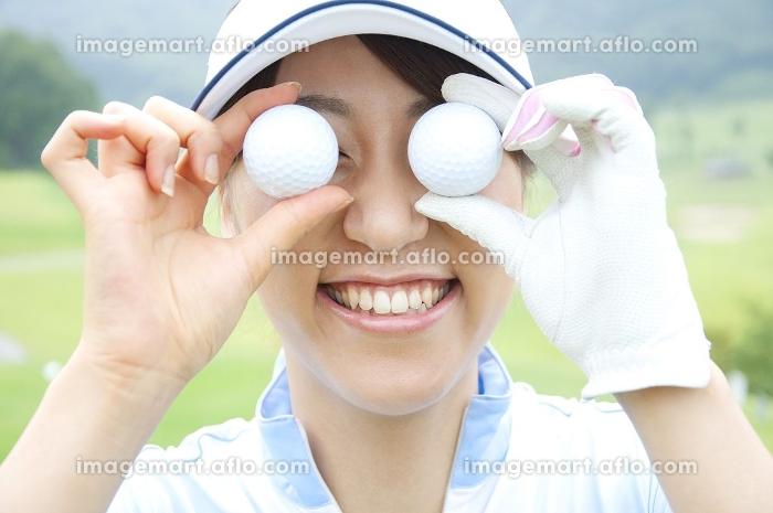 ゴルフボールを目に当てる女性の販売画像